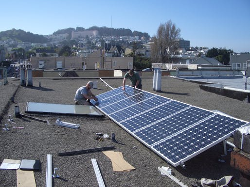 Workers installing solar cells on an existing home. Image courtesy of Flickr user brian kusler.