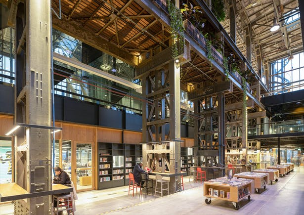 In this book street, books are also checked in and out. The bookcase wall on the office side has transparent display cases for works of art and unique books. This wall also gives staff the right balance between privacy and connection with the library.