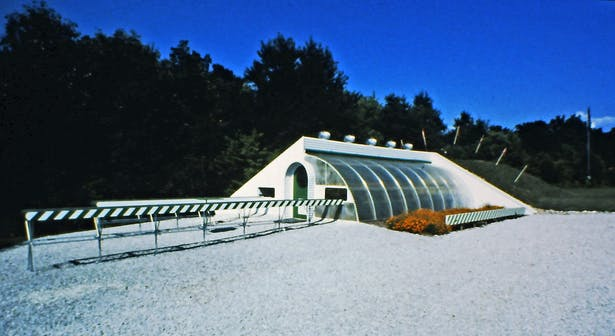 Commercial greenhouse built in 1980. The plants could be moved on a large mobile platform in and out of a underground tunnel from day to night in order to keep the plants warm during the winter without supplemental heat.
