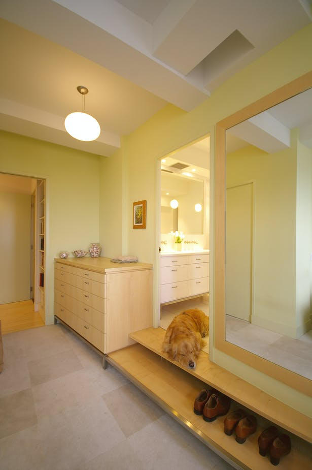 Since the primary bathroom was entirely new, a raised floor was necessary to accommodate the plumbing. The steps up to this bathroom were incorporated into a clever built-in dresser, while the cantilevered steps became shelves for daily shoe storage. The composition was completed by a large mirror next to the bathroom door that was framed in maple to match the cabinetry and steps.