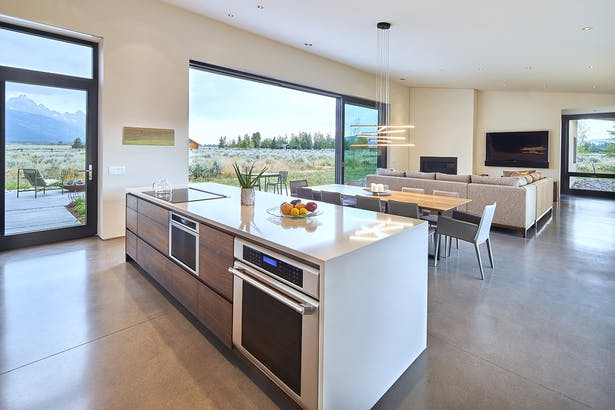 "ust off the kitchen, ""window walls"" of Zola Windows enormous 24-foot triple Zola Lift & Slide door and large fixed units of 8-foot by 10-foot windows–with a custom matte metallic gray."