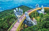 ​Giant weathered hands lift this new golden pedestrian bridge in Vietnam