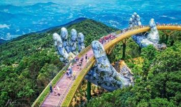 Giant weathered hands lift this new golden pedestrian bridge in Vietnam
