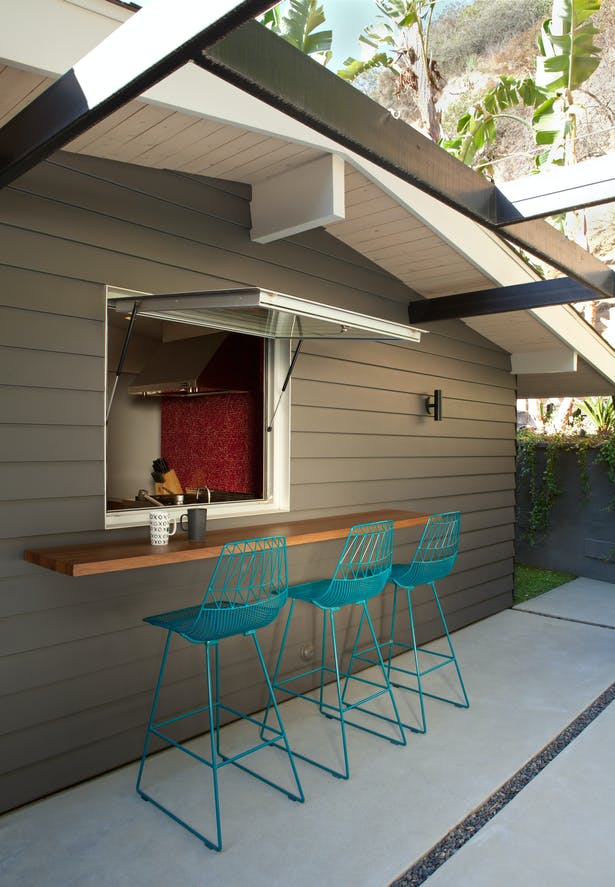 A custom window we designed using automotive hydraulic pistons (used for car trunk doors) that keep the awning window open, and aid in it's closing. The window, counter and eating area help connect the kitchen with the outdoor lounge space.