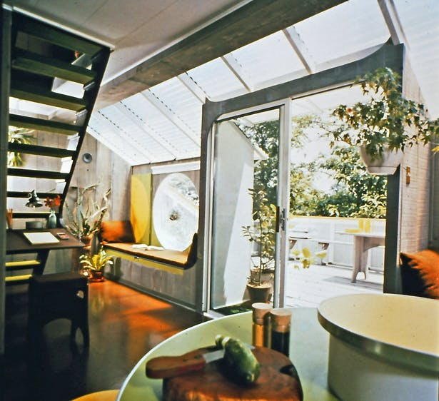 Interior view of the house showing a bubble window, sliding glass door, one of the seats in the closed position, and the corrugated fiberglass glazed roof section.