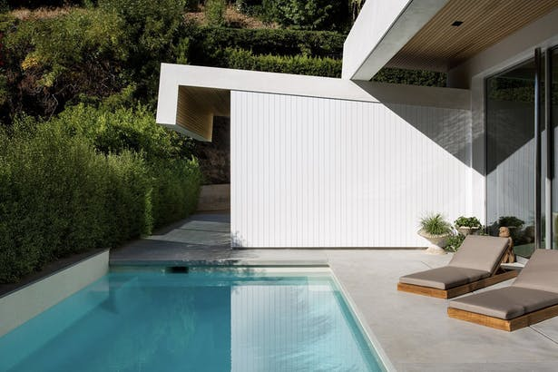'Outside, a tidy backyard patio features the original pool and spa. The home's crisp white facade provide a fresh backdrop for relaxing in the sun.'