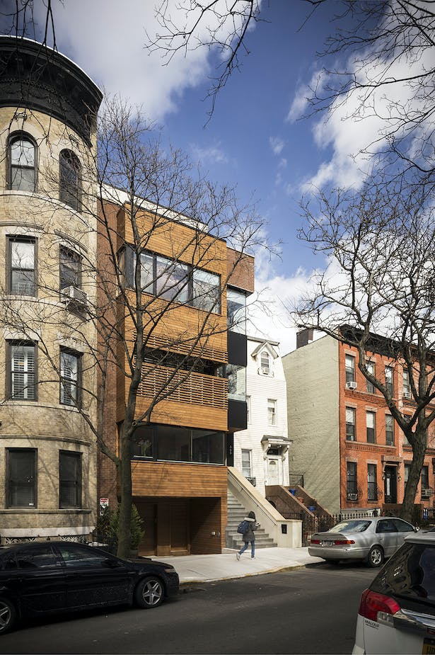 Street Elevation Responds to Context by Aligning with Cornice of Neighboring Townhouses