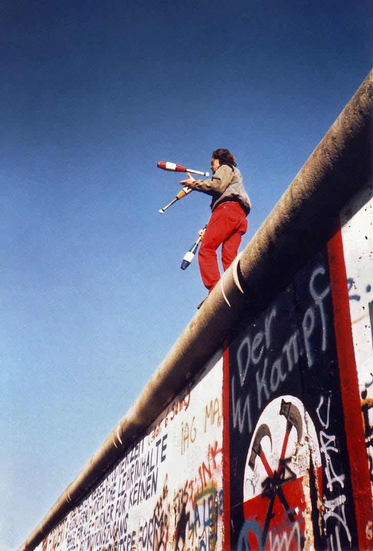 Man juggling atop the Berlin Wall. Image: Wikipedia