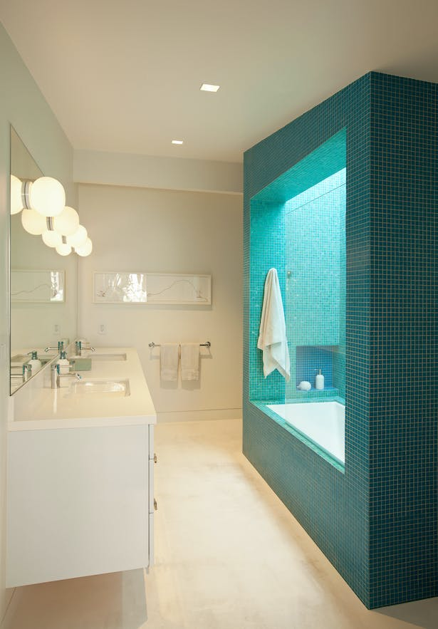 The children's bathroom had no direct window to the outside. So the shower/bath was conceived as a massive inhabitable lightwell, with two colors of mosaic glass tile for the outside and inside. It was designed with the client's eight year old daughter, and the metaphor of a geode was embraced.