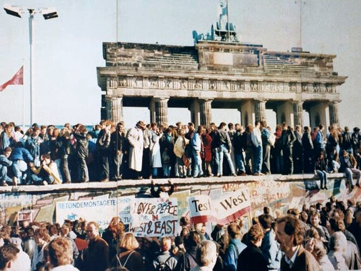 Exuberant Berliners on top of the Wall before it was demolished. Credit: HistoryToday