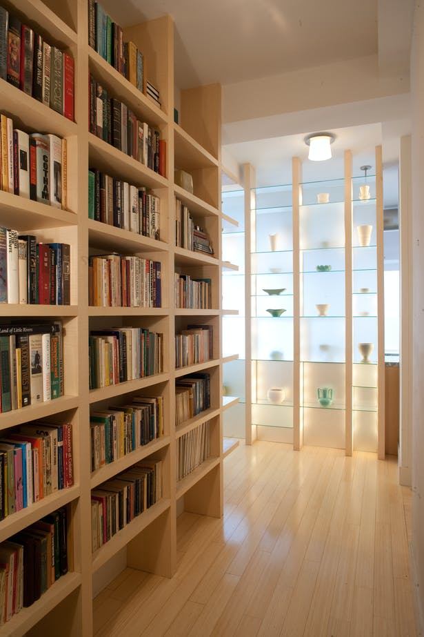 New bookshelves and a translucent shelf wall lead visitors to the main living space while obscuring direct views into the kitchen. The cubistic etched glass shelf wall is backlit by daylight, or it can glow from within by way of cleverly concealed accent lights built into the vertical supports.