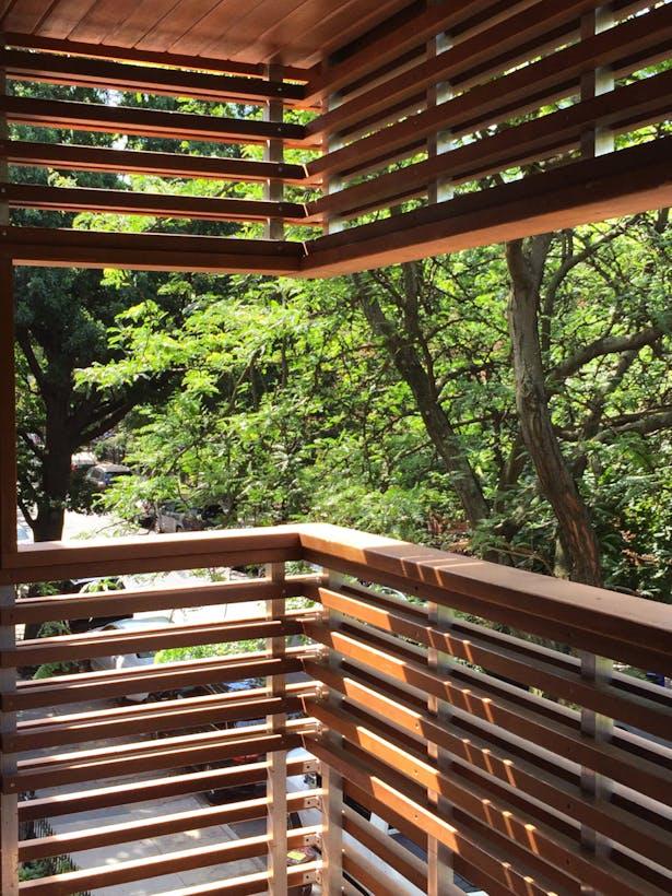 Second Floor Balcony Wrapping in Cedar Slats Overlooking Street