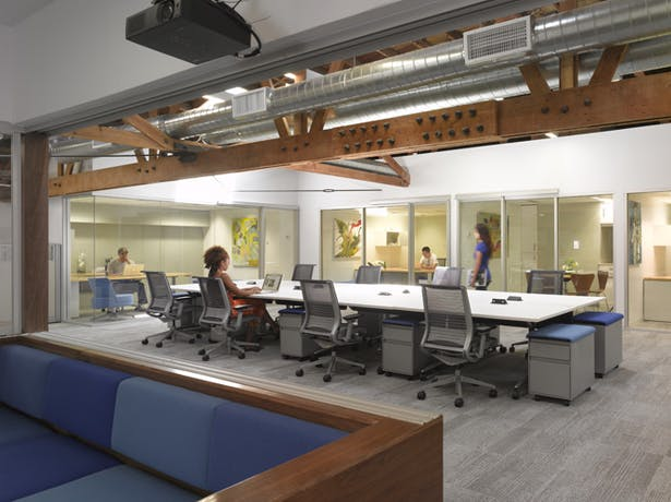 Shared desks with private offices in the background