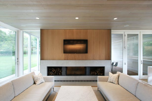 The Fireplace Wall in the Living Space is Composed of Black Steel Log Niches, Gray Marble, and White Oak