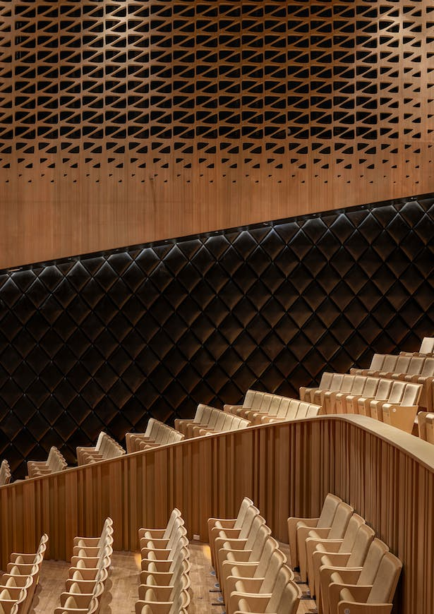 The seats in the Recital Hall have the same golden fabric as the Concert Hall and oak lines the walls. The upper part of this hall is enclosed by a circle of sound absorbing curtains, allowing for the reverberation time within the space to be tuned to specific types of performance. Image by Ethan Lee.