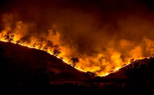 Tree ridge in flames during the 2018 Woolsey Fire in California. Photo courtesy of Peter Buschmann/Wikimedia Commons.
