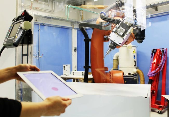 A student at the Vienna University of Technology uses an iPad to control a robot arm. Photo: TU Vienna