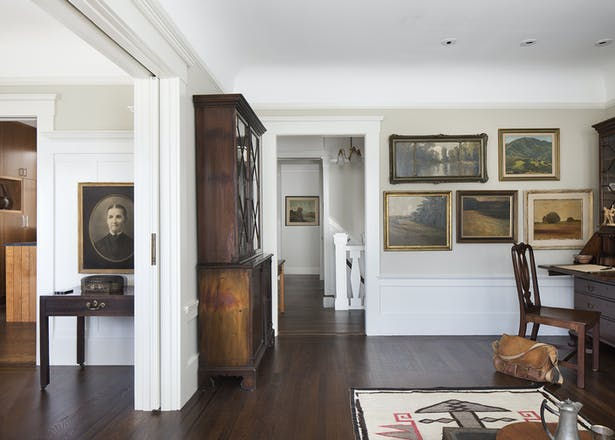 On the upper floor, the entry hall, formal living room and dining room at the front of the house maintain their authentic character and detailing, albeit brighter through the painting of dark wood with lighter hues.
