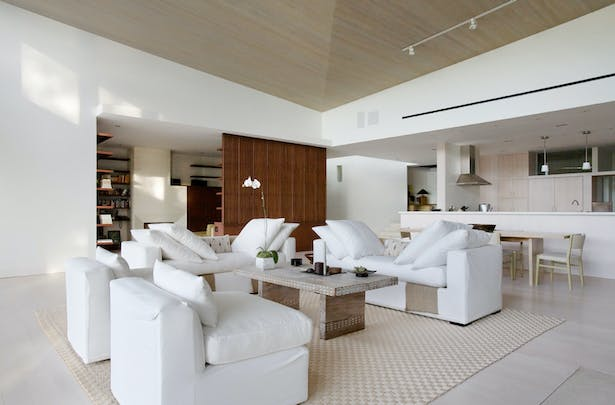 The house is compact, single-story, but the height and variety of ceiling slopes creates a rich spatial experience, and helps give hierarchy to the rooms. Here is the living room, with its sloping wood ceilings, and views into the kitchen to the right, and library to the left.