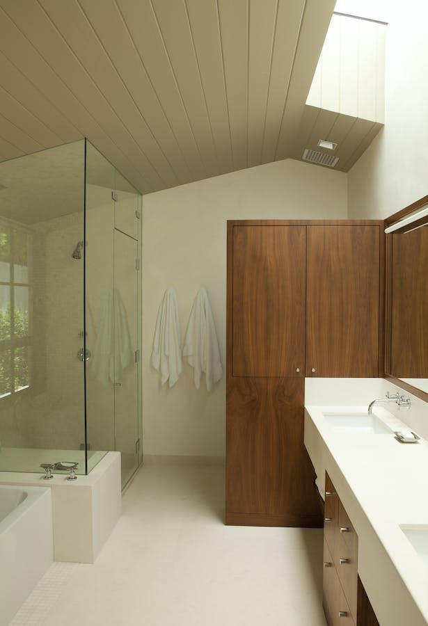 The master bathroom integrates stone, wood, and light with its Douglas fir vaulted ceiling, a freestanding walnut cabinet, a limestone counter and floor, and custom skylights.