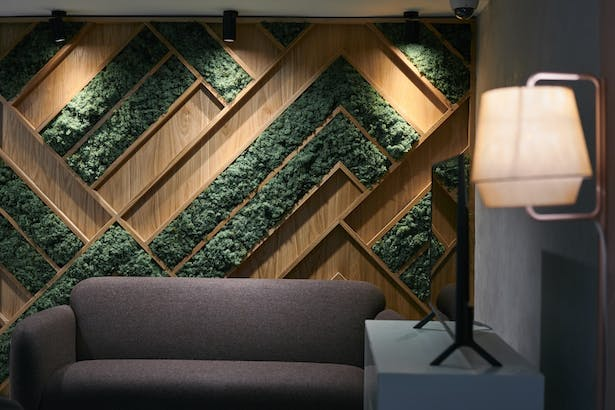 Feature moss and oak wall with subtle lighting - entrance lobby