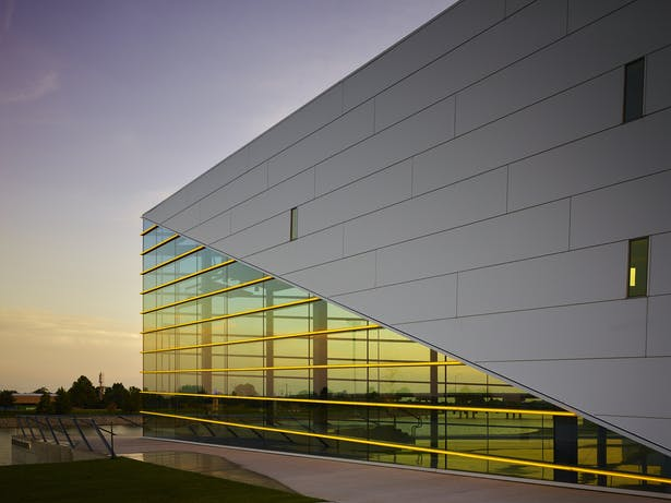 "The sculptural building prow incorporates symbolic lines as if ripples in the water. A surprising overlap of two gold window ""notes"" make the interior volume known."