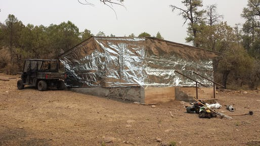 Lolo Engine 416 firemen wrap a cabin in Aluminized Structure Wrap (cabin wrap) to protect the building from radiant heat and burning embers from the Silver Fire. Photo courtesy of the U.S. Department of Agriculture