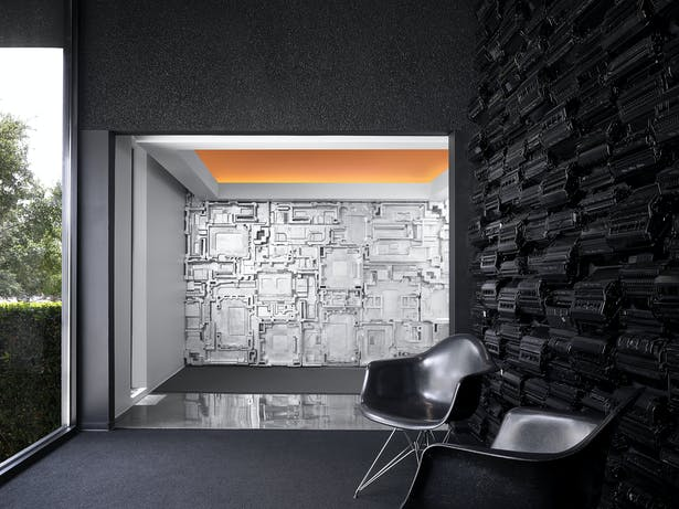 A wall of recycled toner cartridges contrasts with nature. A single toner cartridge takes 450 years to decompose. Recycling 1 cartridge saves 3.6 lbs. of solid waste. Painted formed foam packing is reused as a sculptural wall finish. A statement about sustainability.