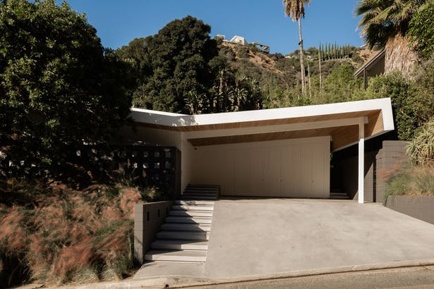 'An original butterfly roof defines the midcentury structure, which is sited on a winding street above the Sunset Strip in Hollywood. Standard Architecture retained this core geometric feature, adding cedar siding underneath overhangs and white edges to emphasize the lines.'