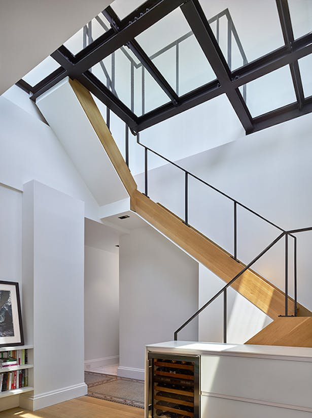 The primary intervention was the construction of an enlarged roof bulkhead, complete with large sliding doors and a glass floor, which floods the living space below with dramatic natural light.