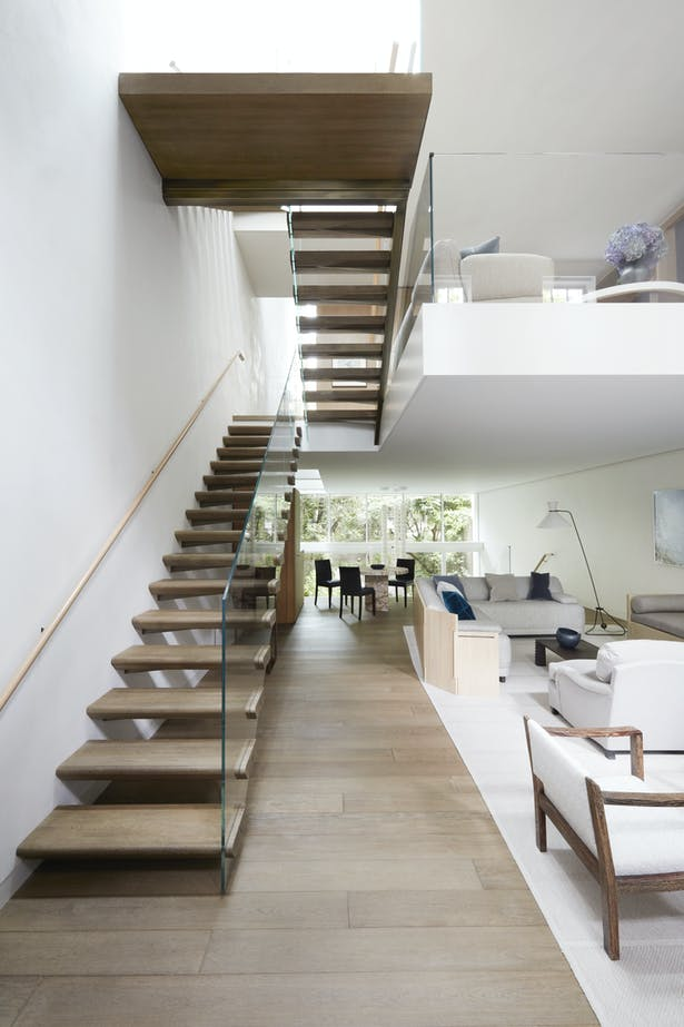 The floating treads and glass balustrade of the main staircase help to maximize the natural light flowing down through the house.