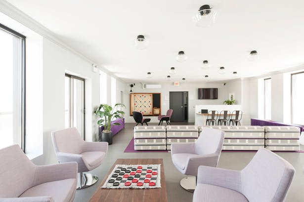 Lounge chairs form a casual meeting space around a large coffee table. At the opposite end, another gaming area is formed around an oversized Scrabble board. The existing radiators, one functioning and one not, where both painted bright purple calling attention to the side walls and views to the lake and the city.