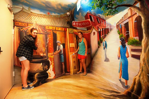 Two girls taking photos with 3D wall painting, which depicts a traditional Taiwanese temple and old street in Taipei.