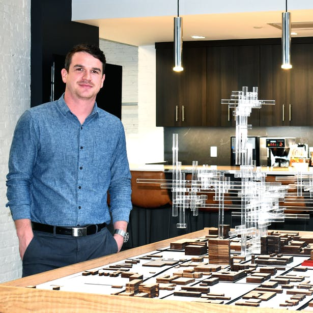 Newly licensed architect Mark Thomas with a speculative model he helped design for an event at the Speed Art Museum.