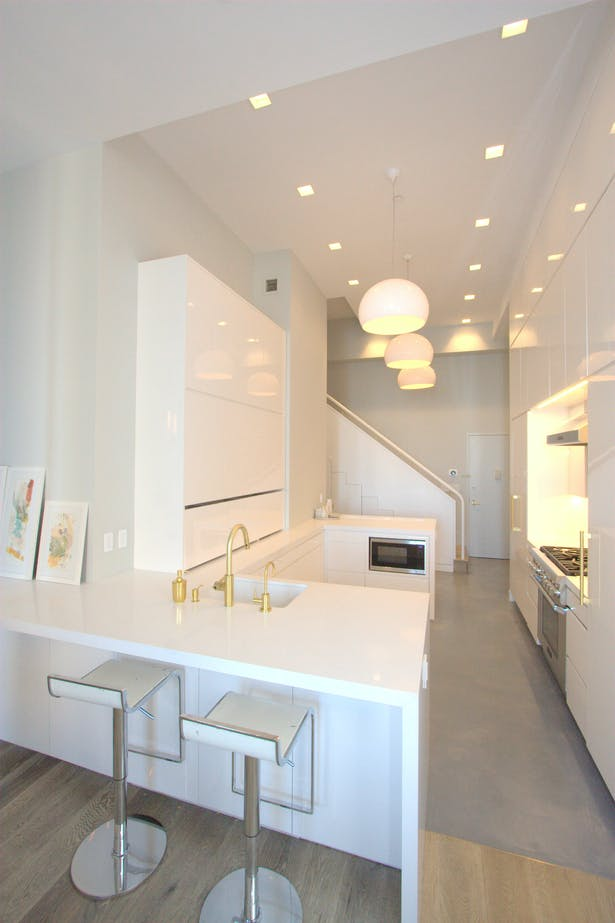 Smooth, white kitchen and polished concrete floor; relocating the entry door allowed us to push the kitchen into a space that had been a foyer and bathroom.