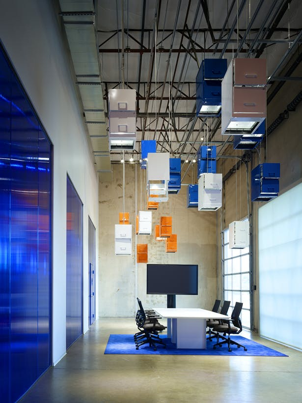 """The original delivery dock is transformed into a primary conference and presentation space. A """"cloud"""" made of pre-owned filing cabinets suspended from the ceiling represent the transition from paper-based systems to storing information digitally in the cloud."""
