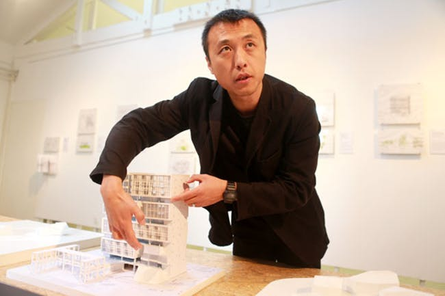 Li Hu displays a model of the Deep Ocean Research Base, one of Open Architecture's projects, at Studio-X Beijing. Feng Yongbin / China Daily