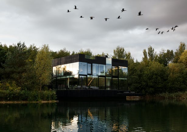 The exterior of the house is designed to disappear/minimally interfere into/with the landscape with the trees, lake and sky reflecting on the glass facades. Image by mariashot.photo