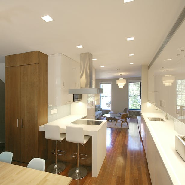 Crisp, white kitchen with walnut accents at the center of the newly open floor plan