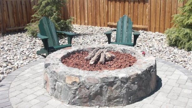 Natural gas fire pit built with chisled granite. This was surrounded by Cedar trees to create a very private feel sectioned off from the house and rest of the backyard