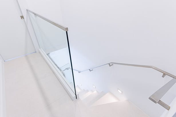 A glass guardrail was also installed on the second floor. This glass panel was top mounted to an aluminum base shoe, then covered with a white coated stainless steel cladding to match seamlessly with the flooring.