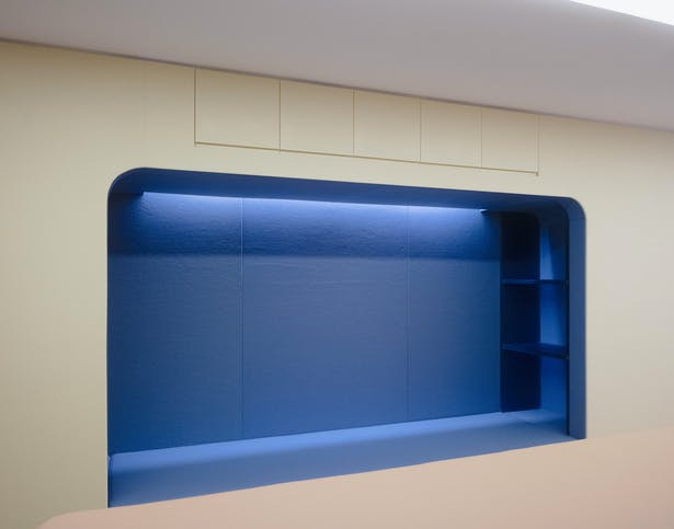 A wide seating nook overlooking the tunnel room with storage cabinets above.