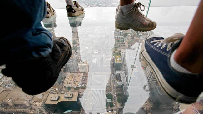 Participants stand on the new glass balconies suspended 1,353 feet in the air and jut out 4 feet from the Willis Tower's 103rd floor Skydeck on July 1, 2009 in Chicago. (Mashable; Image: Kiichiro Sato/Associated Press)