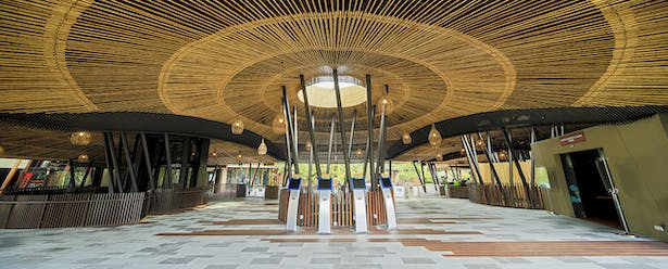 The solid metal roof is transformed into a lightweight canopy by applying extensive treated bamboo screening underneath