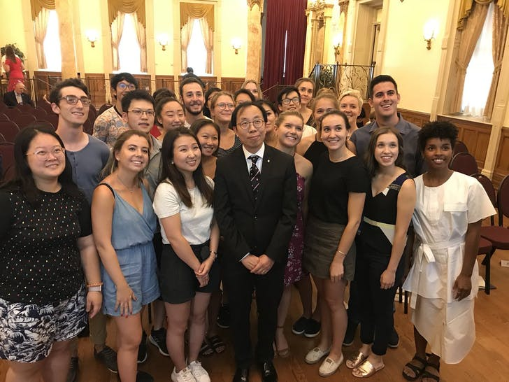 Peter Fu posing with students.