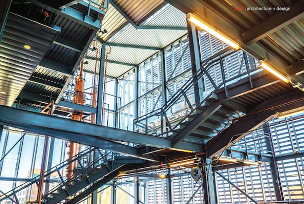 Inside the Manufacturing Atrium. The 48-foot-tall copper still is visible (left) as it rises through the space,