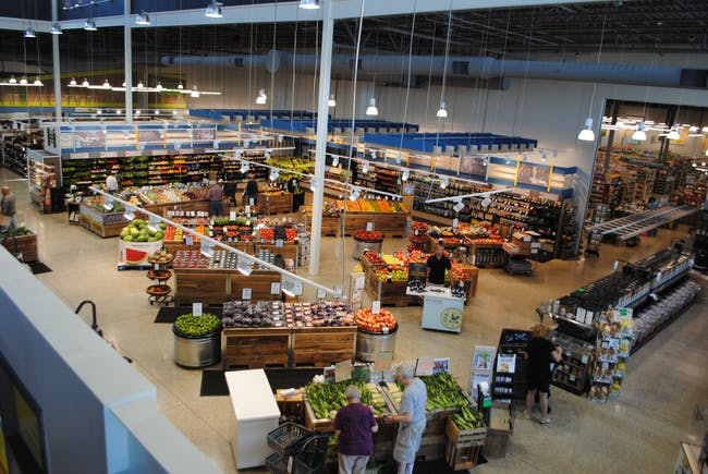 Interior of Harvest Market from the upper mezzanine, where shoppers gather for lunch and board games during the day and glasses of wine at night. (Photo courtesy of Joe Fassler)