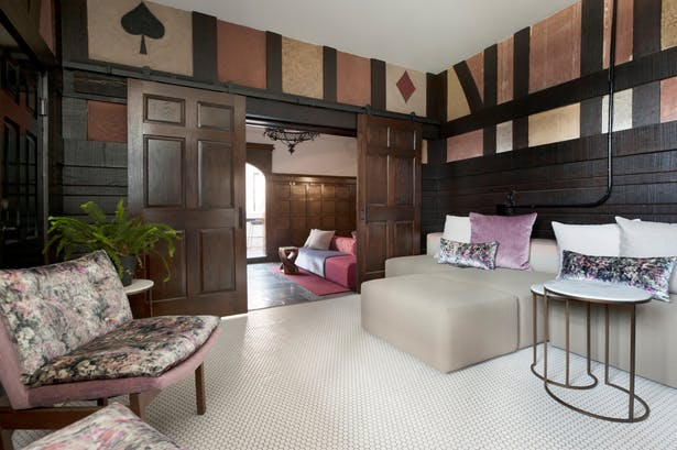 A former storage room off the lobby was transformed into a conversation lounge. The original doors leading to the lobby were re-purposed as sliding doors to accommodate a raised floor level connecting this area with a residential corridor. Half-timbered walls with suits of playing cards were restored and inspired the tones in the velvet accents. Another large sectional from Stylex lines one full wall and is covered in an embroidered Xorel fabric for durability against spills in this secluded...