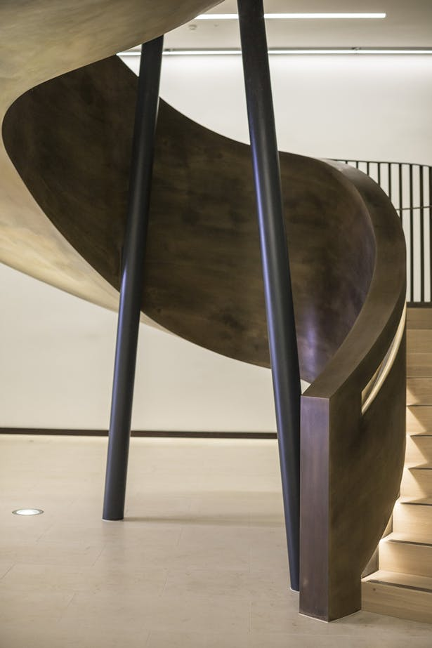 Two steel columns pierce the centre of the staircase