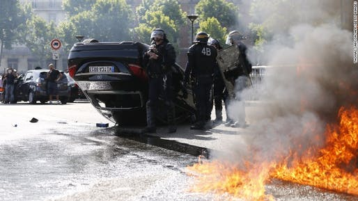 French policemen standing near a car that was overturned during riots by taxi drivers in protest of UberPop. Credit: Thomas Samson / AP